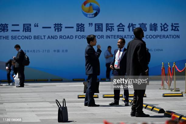 People chat in front of a billboard for the Belt and Road Forum outside the China National Convention Centre in Beijing on April 25 2019 Leaders from...