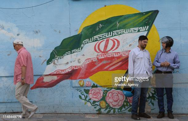 People chat in front of a mural depicting a flag of Iran in Tehran Iran on May 22 2019