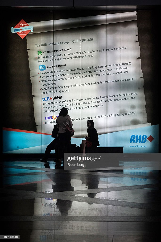 People chat in front of an advertisement for RHB Investment Bank Bhd. at the company's headquarters in Kuala Lumpur, Malaysia, on Monday, May 6, 2013. The biggest surge in Malaysian stocks since 2008 has turned into a money-losing day for investors who piled in at the height of the rally sparked by Prime Minister Najib Razak's election victory. Photographer: Sanjit Das/Bloomberg via Getty Images
