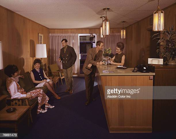 People chat in the lobby of the Grand Motel while a staff member with a beehive hairdo shows a guest pages in a tourbook Myrtle Beach South Carolina...