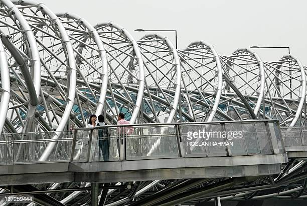 "People chat on an observation deck of a 280-metre long bridge, named ""The Helix"" leading to the Marina Bay Sands integrated hotel and the skypark in..."
