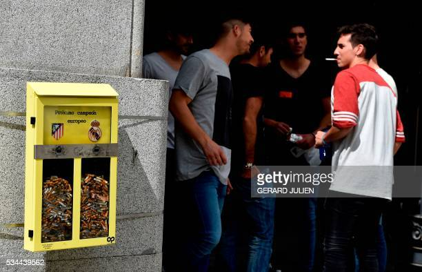 People chat past an ashtray displayed by the City Council and shaped as a ballot box inviting the passerby to vote with their cigarette butt for the...