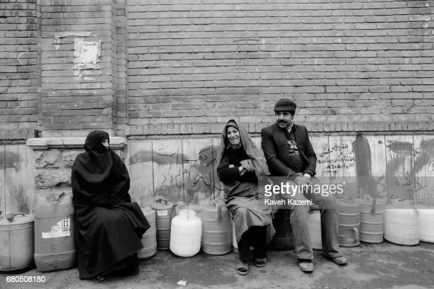 People chat while waiting in line for kerosene sat on plastic containers in Shah Reza avenue in Tehran during the Iranian Revolution 19th January 1979