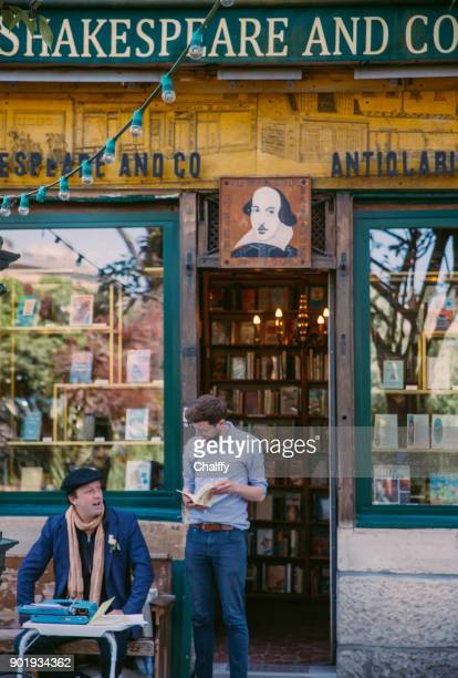 people chatting out of a bookstore in paris - book store stock photos and pictures