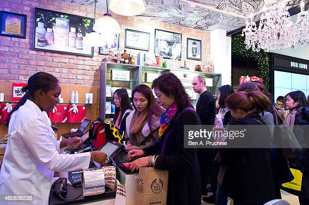 People check at the cashier after shopping at Selfridges during their Boxing Day Sale on December 26 2014 in London England