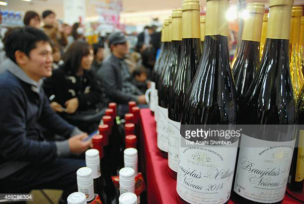 People check bottles of Beaujolais Nouveau after its release at a supermarket on November 20 2014 in Fukuoka Japan The import of the wine used to...