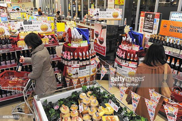 People check bottles of Beaujolais Nouveau after its release at a supermarket on November 20 2014 in Osaka Japan The import of the wine used to...