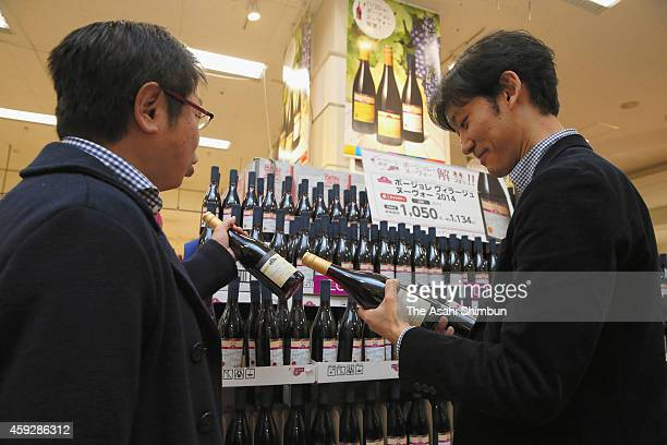 People check bottles of Beaujolais Nouveau after its release at a supermarket on November 20 2014 in Tokyo Japan The import of the wine used to...