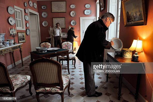 People check furniture and items in a room on September 29 2012 at the Chateau de Varvasse in Chanonat central France during the auction of the...