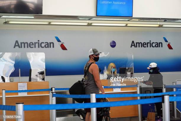 People check in at the American Airlines counter in the Fort Lauderdale-Hollywood International Airport on July 16, 2020 in Fort Lauderdale, Florida....