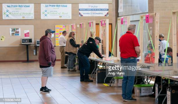 People check in to vote at a polling location on April 7, 2020 in Sun Prairie, Wisconsin. Residents in Wisconsin went to the polls a day after the...
