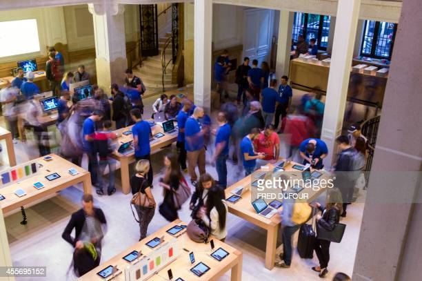 People check items at the Apple Store in Paris on the day of the launch of the latest iPhone the iPhone 6 on September 19 2014 Apple says more than...