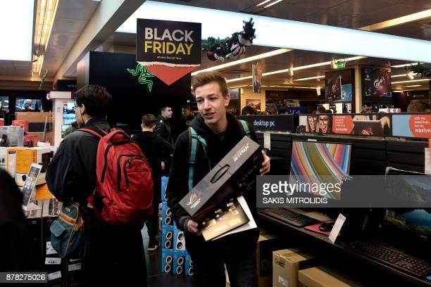 People check items in a department store in Thessaloniki on November 24 2017 Long queues snaked outside department stores for the Black Friday...
