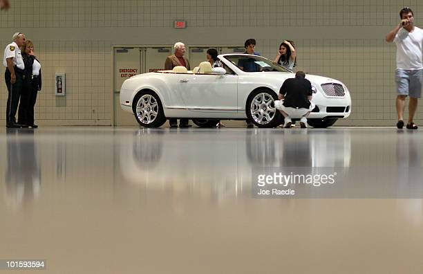 People check out a 2009 Bentley Continental GTC before the auction put on by Rick Levin and Associates Inc on behalf of the US Dept of the Treasury...