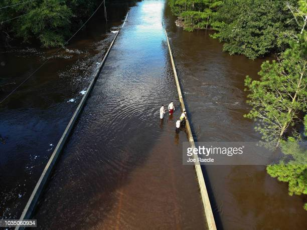 People check out the flooding as the Rockfish creek overflows a roadway on September 17, 2018 in Fayetteville, North Carolina. Flood waters from the...