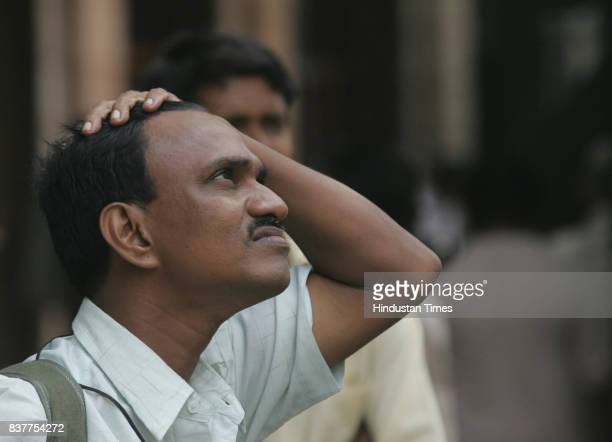 People check out the live index after the Bombay Stock Exchange Sensex collapsed by 366 points in Mumbai on Wensday