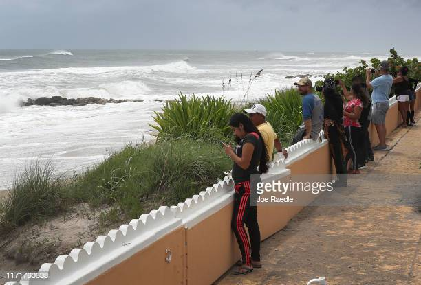 People check out the waves in the ocean as Hurricane Dorian continues to make its way toward the Florida coast on September 02 2019 in West Palm...