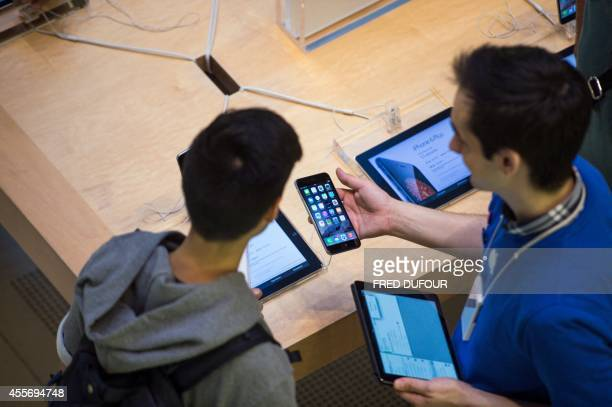 People check the latest iPhone the iPhone 6 on the day of its launch on September 19 2014 in Paris Apple says more than four million preorders were...