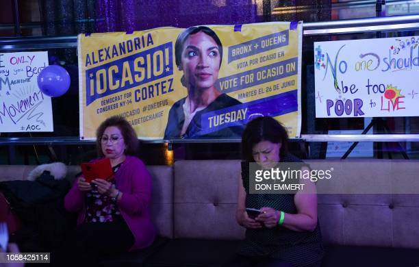 People check the latest mid-terms results on thier phones while celebrating Alexandria Ocasio-Cortez congressional race big win during her election...