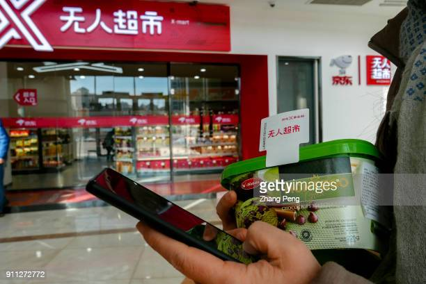 People check the payment information on smart phone after shopping in X supermarket On January 18th Jingdong X selfservice supermarket opened in...