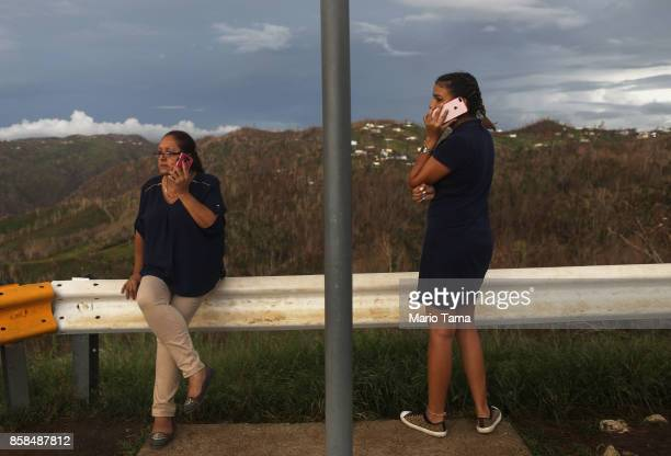People check their cell phones from a roadside near the top of a mountain more than two weeks after Hurricane Maria swept through the island on...