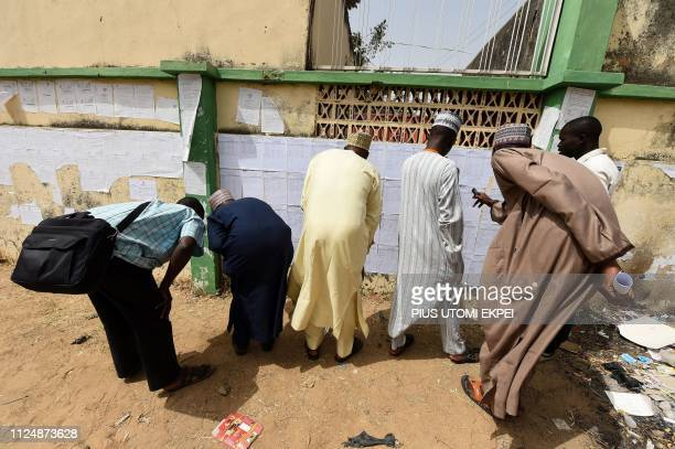 People check their names on voters' list displayed on a board at the headquarters of Independent National Electoral Commission in Kano Nigeria on...