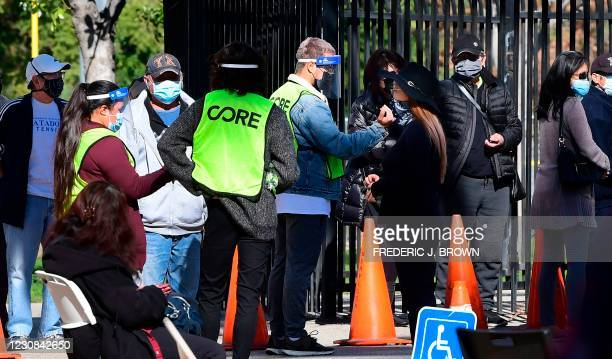 People check-in at a Covid-19 walk-up testing site at Lincoln Park in Los Angeles, California on January 28, 2021. - The daily number of deaths from...