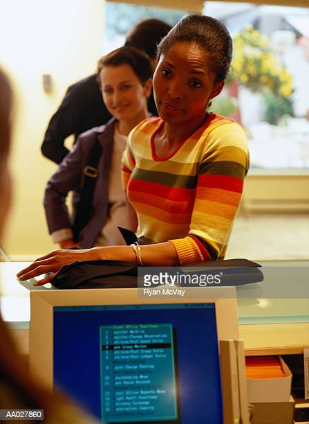 People Checking Into a Hotel at Reception Desk