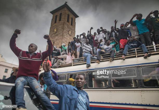 People cheer a passing Zimbabwe Defense Force military vehicle during a demonstration demanding the resignation of Zimbabwe's president on November...