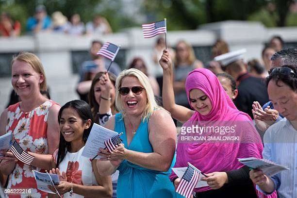 People cheer after taking the oath of citizenship during a naturalization ceremony at the World War II Memorial on the National Mall August 25 2016...