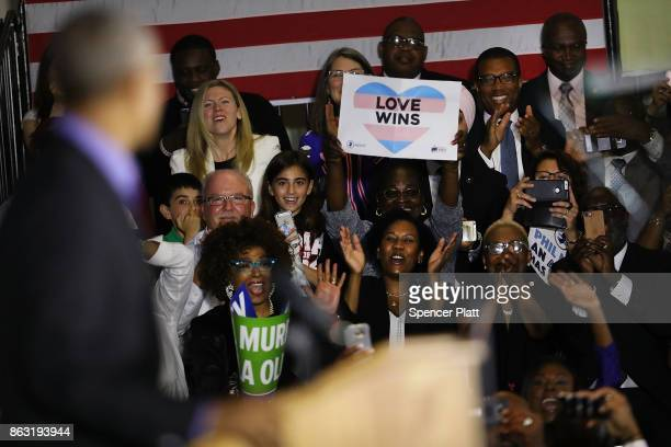 People cheer and take pictures as Former US President Barack Obama speaks at a rally in support of Democratic candidate Phil Murphy who is running...