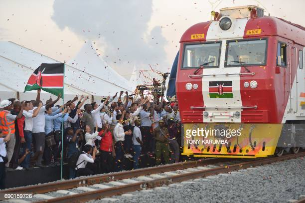 People cheer and throw confetti after Kenyan President Uhuru Kenyatta flags off a cargo train for its inaugural journey to Nairobi at the port of the...