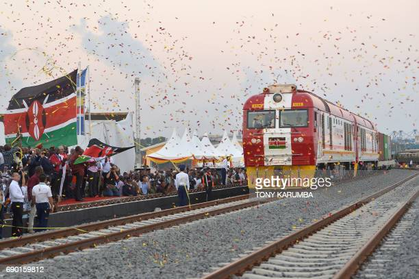 People cheer and throw confetti, after Kenyan President Uhuru Kenyatta flags off a cargo train for its inaugural journey to Nairobi, at the port of...