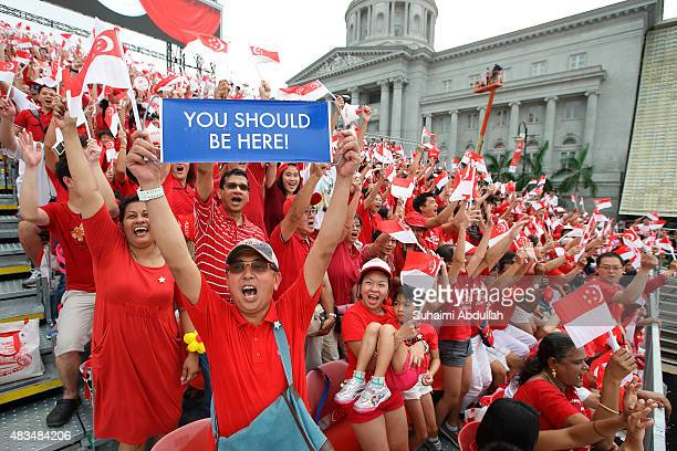 People cheer and wave the flags during the National Day Parade at Padang on August 9 2015 in Singapore Singapore is celebrating her 50th year of...