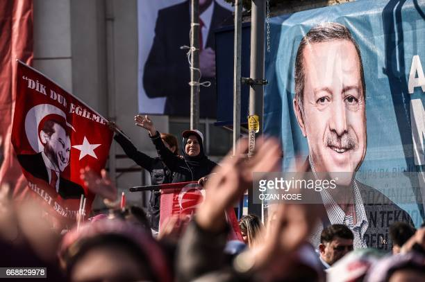 People cheer and wave Turkish national flags by a campaign poster depicting Turkish President Recep Tayyip Erdogan during a rally on April 15 in...