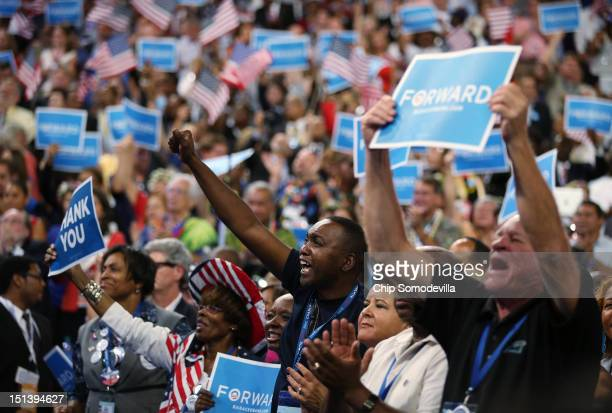 People cheer as Democratic presidential candidate US President Barack Obama speaks on stage as he accepts the nomination for president during the...