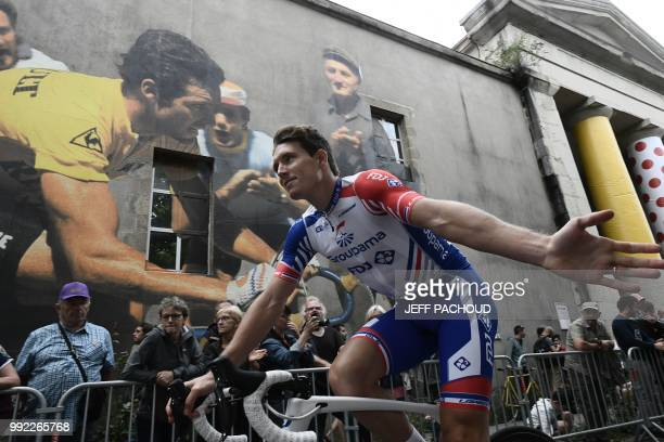 People cheer as France's Arnaud Demare of France's Groupama - FDJ cycling team cycles past during the team presentation ceremony on July 5, 2018 in...