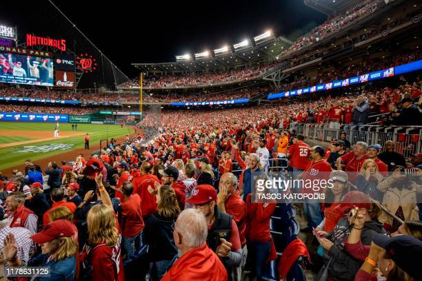 People cheer as members of the military are recognized during Game 5 of the World Series between the Washington Nationals and Houston Astros at...
