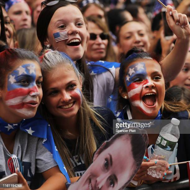 People cheer as members of the US Women's National Soccer Team travel down the Canyon of Heroes in a ticker tape parade on July 10 2019 in New York...