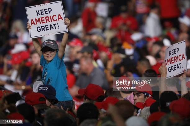 People cheer as President Donald Trump prepares to speak to supporters at a rally in Manchester on August 15 2019 in Manchester New Hampshire The...