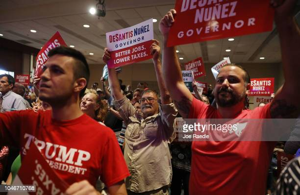 People cheer as Republican gubernatorial candidate Ron DeSantis speaks during a campaign rally at the Palm Beach County Convention Center on October...