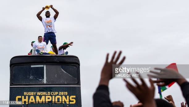People cheer as South African Rugby captain Siya Kolisi holds up the Web Ellis Trophy while the South African Rugby World Cup winner team parades on...