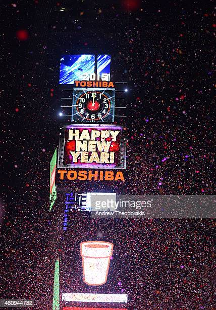 People cheer as the ball drops at midnight in Times Square on January 1 2015 in New York City An estimated one million people from around the world...