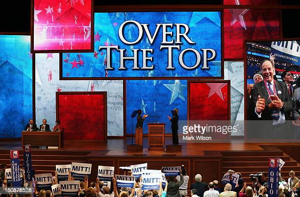 """People cheer as the sceen displays """"Over The Top"""" during roll call of delegates at the Republican National Convention at the Tampa Bay Times Forum on..."""