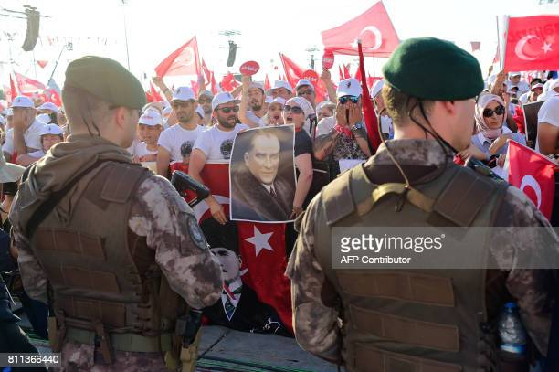 TOPSHOT People cheer as Turkey's main opposition Republican People's Party leader Kemal Kilicdaroglu throws flowers to supporters during a rally on...
