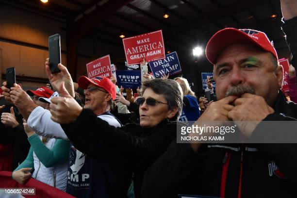 People cheer as US President Donald Trump arrives to speak at a campaign rally at the Huntington Tri-State Airport, on November 2 in Huntington, West...