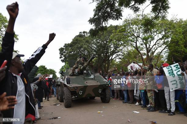 People cheer as Zimbabwean soldiers arrive on a tank during a march in the streets of Harare on November 18 2017 to demand to the 93 yearold...