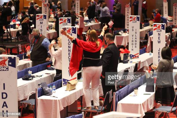 People cheer at President Donald Trump's speech to delegates on the first day of the Republican National Convention at the Charlotte Convention...