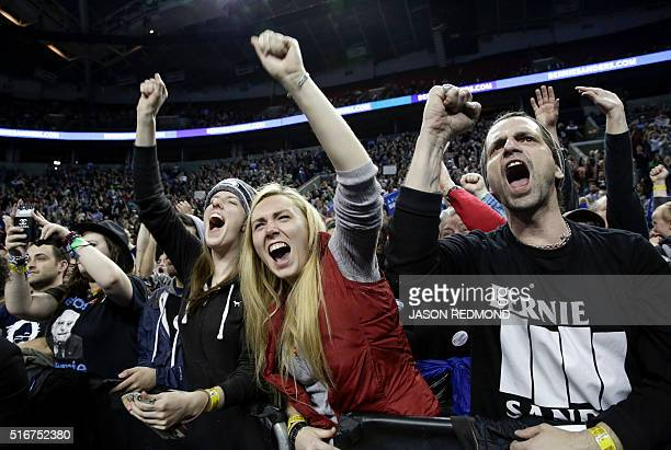 TOPSHOT People cheer during a rally for Democratic presidential candidate Bernie Sanders at Key Arena on March 20 2016 in Seattle / AFP / Jason...