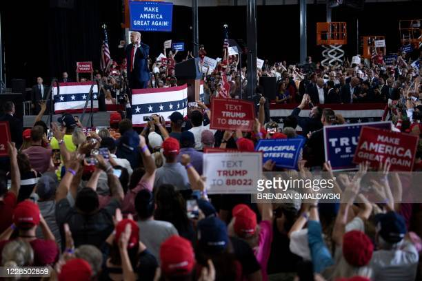 People cheer for US President Donald Trump after he spoke during an indoor campaign rally at Xtreme Manufacturing in Henderson, a suburb of Las...